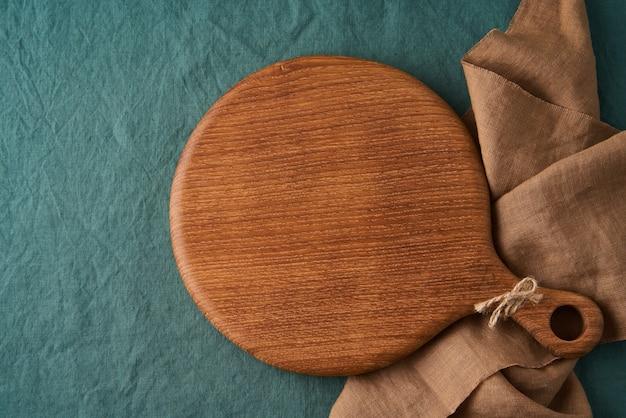 Maquette de fond de nourriture avec planche à découper en bois ronde sur nappe textile en lin vert foncé