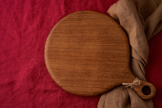 Maquette de fond de nourriture avec planche à découper en bois ronde sur textile de canneberge rouge vif lin