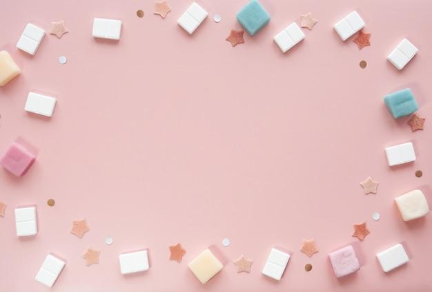 Maquette de fond rose mignonne avec des bonbons et des étoiles