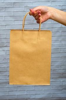 Maquette en gros plan d'emballage écologique sur un fond gris brique. sac kraft dans la main d'une femme. concept d'achat en ligne, livraison, commandes en ligne.