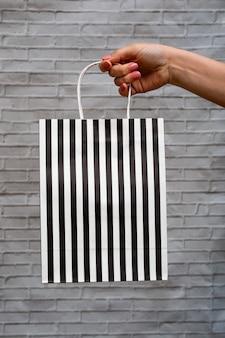 Maquette en gros plan d'un emballage écologique sur fond gris brique. sac kraft à rayures noires et blanches dans une main de femme. shopping en ligne