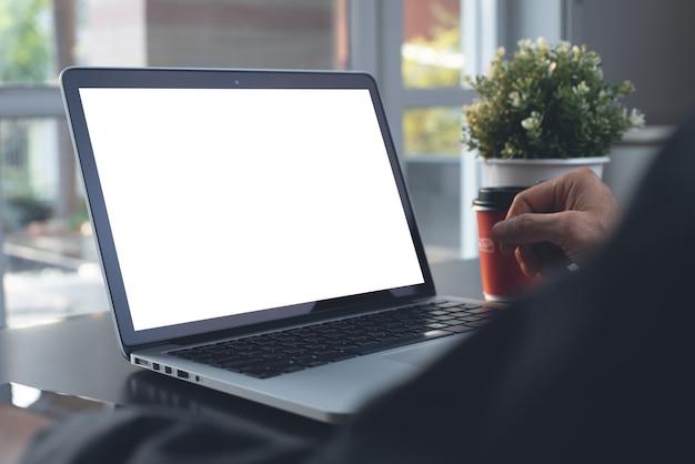 Maquette d'un homme d'affaires travaillant sur un ordinateur portable à écran blanc au bureau à domicile en gros plan