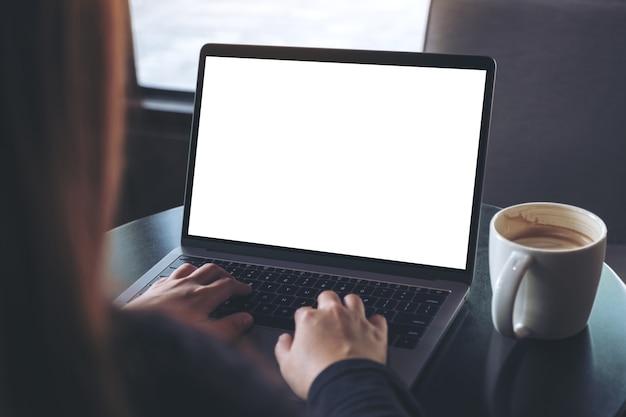 Maquette image de femme d'affaires en utilisant et en tapant sur un ordinateur portable avec écran blanc vierge