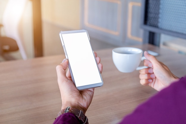 Maquette image des mains de l'homme tenant un téléphone portable blanc avec la technologie d'écran blanc