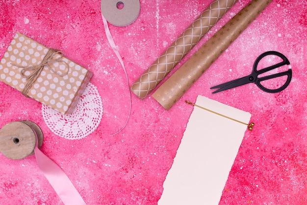 Maquette d'invitation d'anniversaire à côté des fournitures d'emballage cadeau