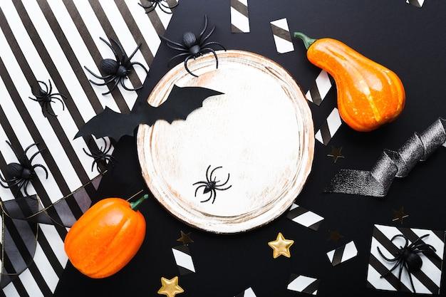 Maquette d'invitation à la fête d'halloween, célébration. concept de décorations d'halloween avec chauves-souris, araignées, citrouilles, étoiles, confettis, ruban. mise à plat, vue de dessus, espace de copie sur fond noir et blanc.