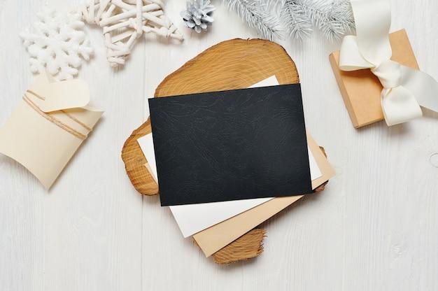 Maquette lettre de carte de voeux de noël noir en enveloppe et cadeau avec arbre blanc