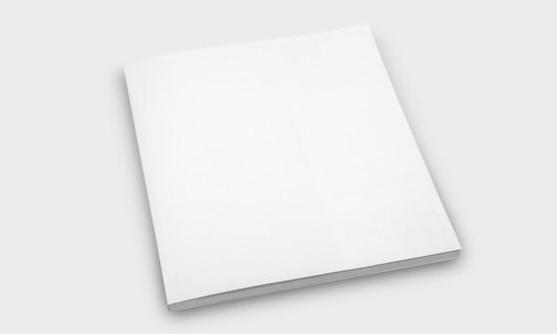 Maquette de livre carré vierge fermé sur fond de papier texturé blanc.