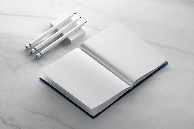 Maquette de livre de journal vierge avec des crayons sur une surface en marbre