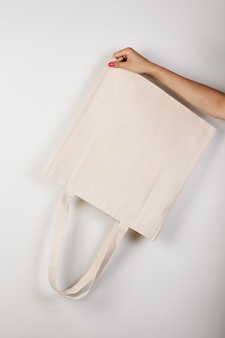 Maquette main féminine avec une belle manucure tient un éco-sac blanc inversé fait de matériaux recyclés sur...