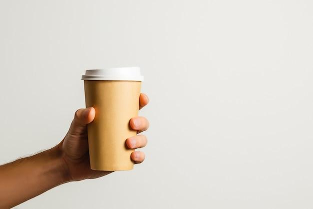 Maquette de main masculine tenant une tasse de papier café isolée sur fond gris clair