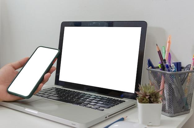 Maquette main tenant un écran blanc de smartphone et un ordinateur portable sur le bureau.