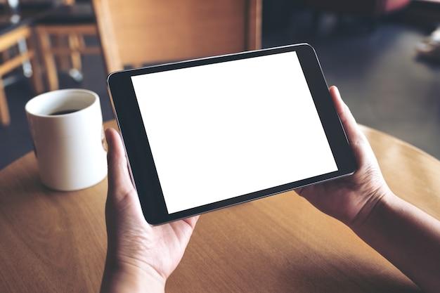 Maquette de mains tenant un tablet pc noir avec écran blanc vierge et tasse à café sur table