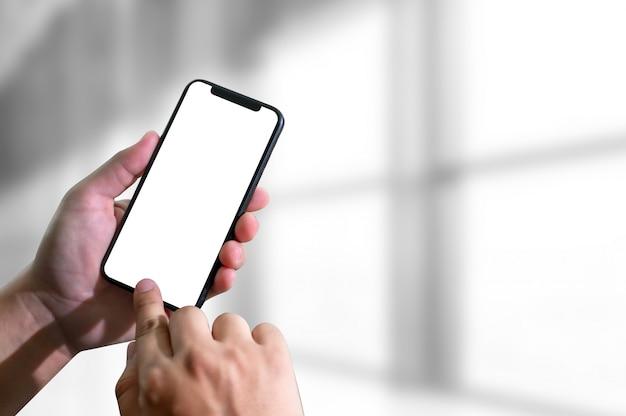 Maquette mains tenant un téléphone portable avec écran blanc