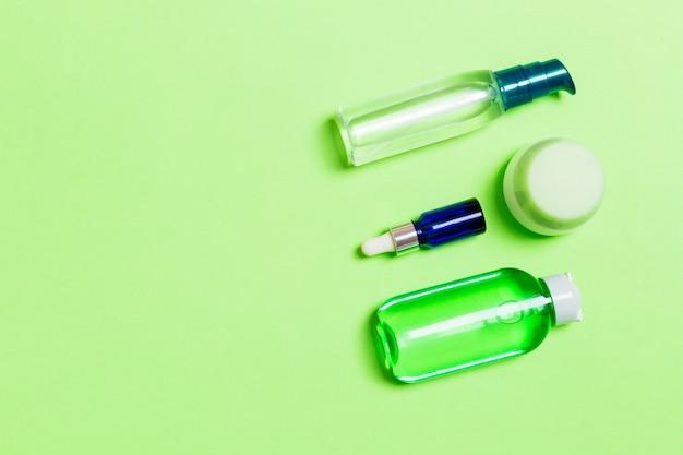 Maquette de marque cosmetics spa, vue de dessus avec espace de copie. ensemble de tubes et de pots de crème à plat sur fond vert.