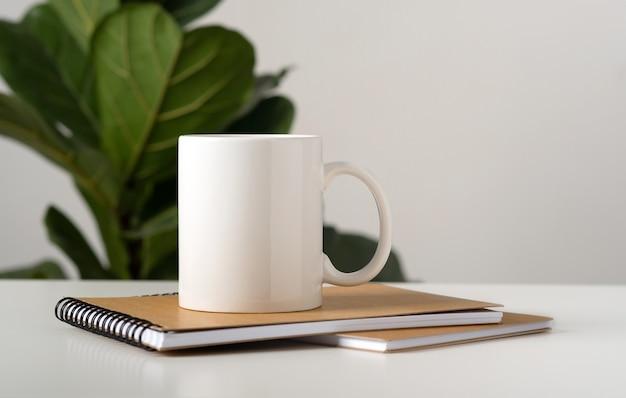 Maquette d'un mug blanc sur une table dans un intérieur minimaliste, blocs-notes d'affaires, ficus lyrata compacta.