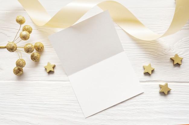 Maquette de noël carte de voeux vue de dessus et étoile d'or, flatlay sur un fond en bois blanc avec un ruban
