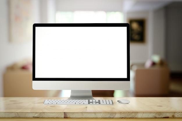 Maquette d'ordinateur de bureau à écran blanc sur une table de bureau en bois au-dessus du salon.