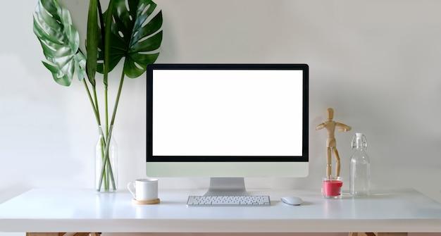 Maquette d'ordinateur à écran blanc en milieu de travail élégant