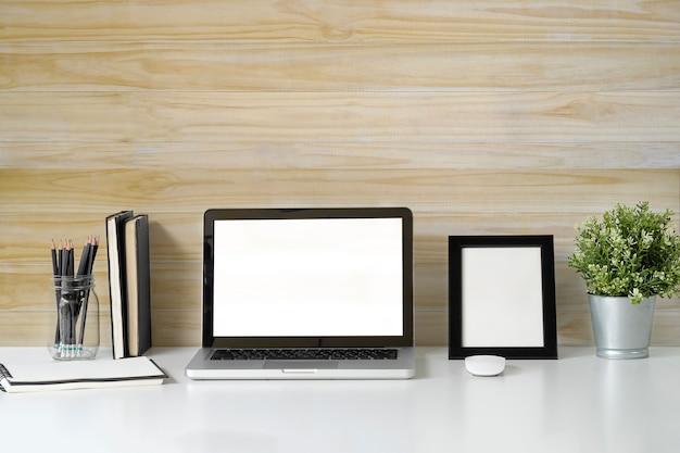 Maquette ordinateur portable sur le bureau haut blanc et mur en bois avec des accessoires de livre et d'artiste.