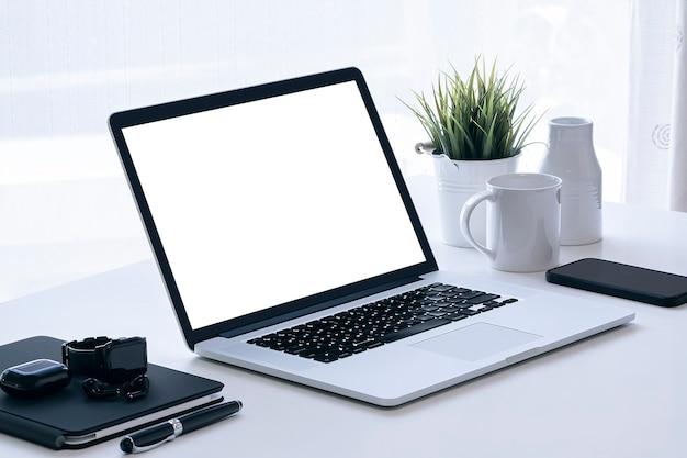 Maquette ordinateur portable écran balnk et gadget sur table blanche avec fond clair.