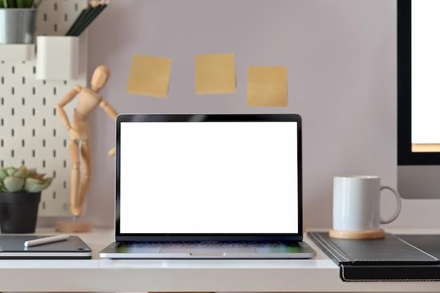Maquette d'ordinateur portable à écran blanc sur le bureau de loft