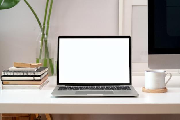 Maquette d'ordinateur portable à écran blanc dans l'espace de travail du loft
