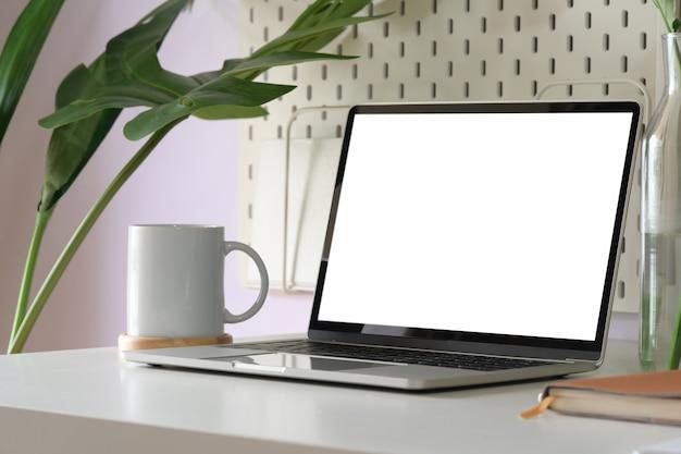 Maquette d'ordinateur portable à écran blanc dans l'espace de travail de loft