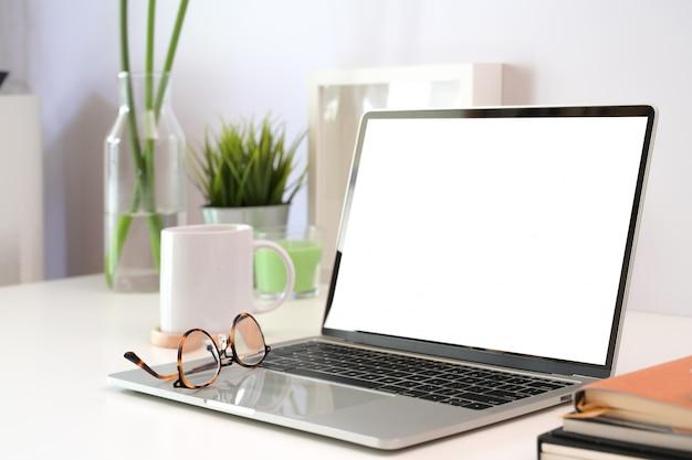 Maquette d'ordinateur portable à écran blanc sur un espace de travail minimal
