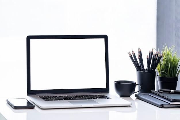 Maquette ordinateur portable écran blanc et fournitures noires sur tableau blanc.