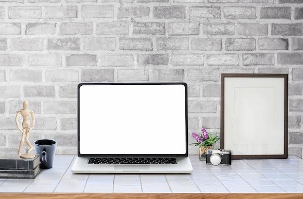 Maquette ordinateur portable à écran blanc avec des fournitures sur une table blanche.