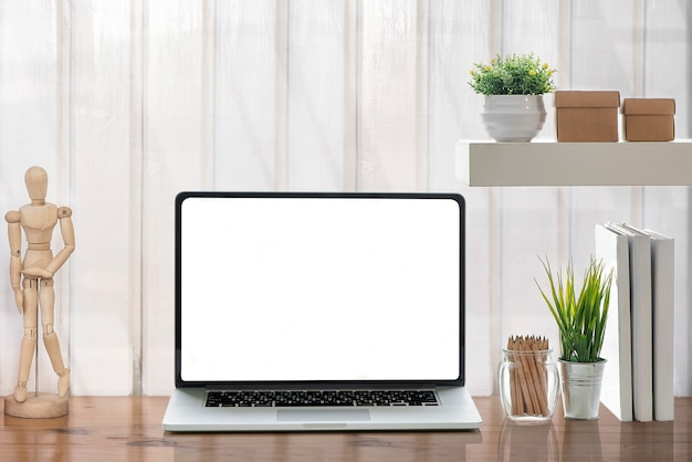 Maquette ordinateur portable avec écran blanc et fournitures sur table blanche.