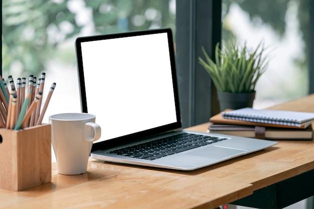 Maquette d'ordinateur portable à écran blanc sur une table de comptoir en bois dans un espace de travail partagé.
