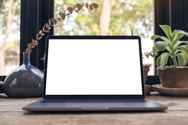 Maquette d'ordinateur portable avec écran de bureau blanc blanc et tasse à café sur table en bois vintage