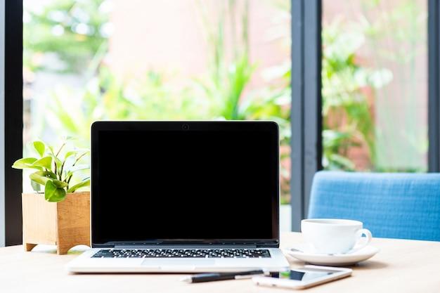 Maquette d'ordinateur portable avec écran vide avec tasse de café sur la table du café