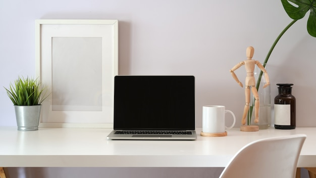 Maquette d'ordinateur portable sur l'espace de travail blanc loft
