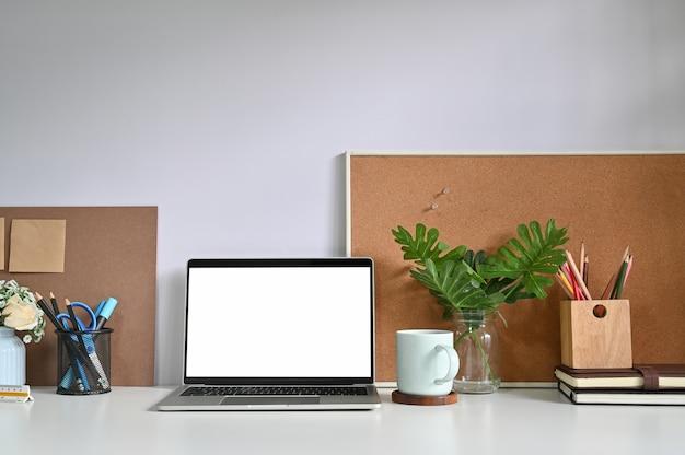 Maquette d'ordinateur portable sur un espace de travail et des fournitures de bureau.