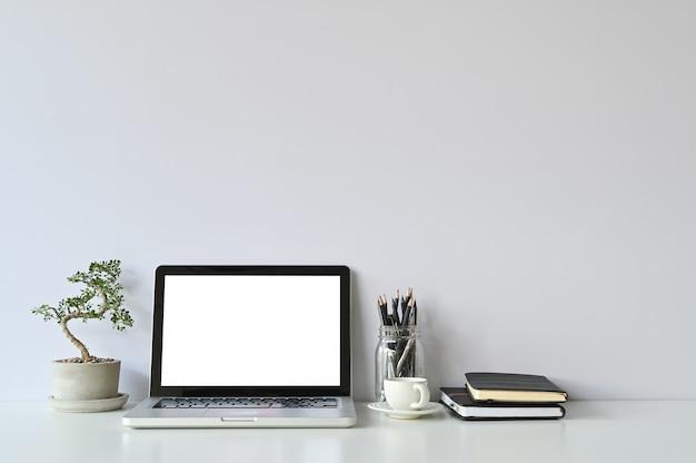 Maquette ordinateur portable et fournitures de bureau et petit bonsaï sur espace de travail.