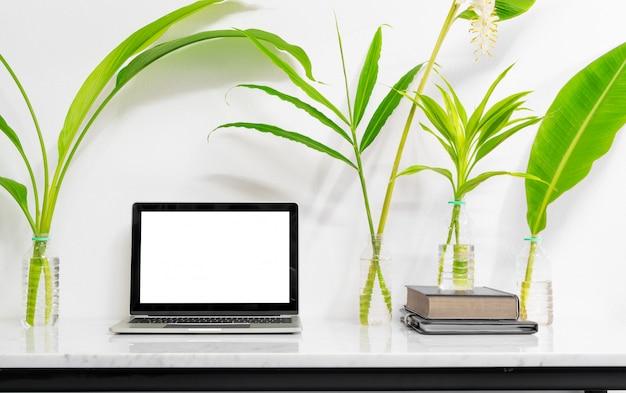 Maquette ordinateur portable avec des fournitures et des plantes sur la table de bureau en marbre.
