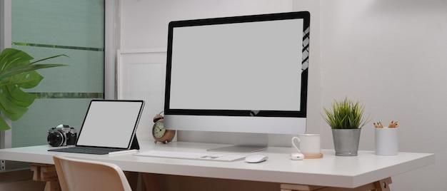 Maquette ordinateur portable, ordinateur, appareil photo et décorations sur un bureau blanc dans la salle de bureau à domicile