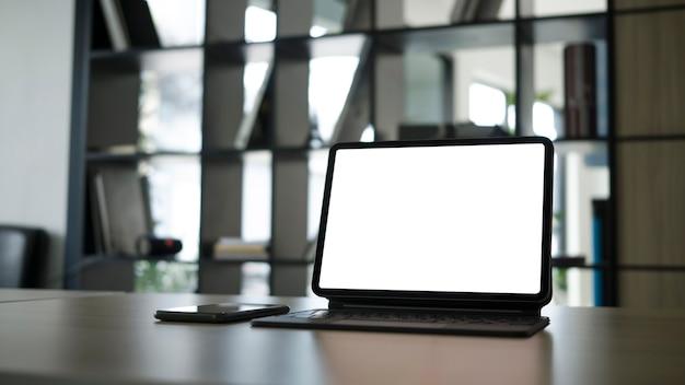 Maquette d'ordinateur tablette avec écran blanc et téléphone intelligent sur un bureau blanc.