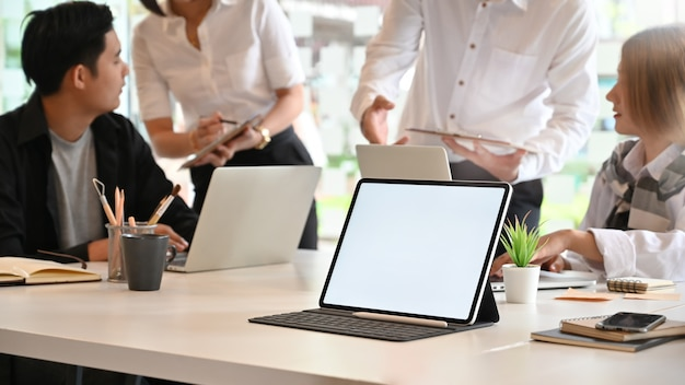 Maquette ordinateur tablette sur la salle de réunion avec des gens qui se rencontrent, tablette écran vide.