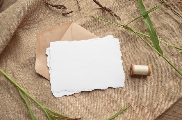 Maquette de papeterie d'été avec des herbes, bobine vintage sur fond beige à partir de tissu de jute