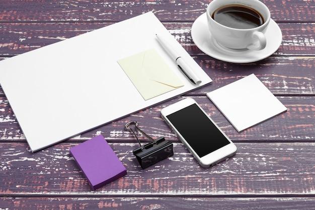 Maquette de papeterie de marque sur un bureau violet. vue de dessus du papier, carte de visite, bloc-notes, stylos et café.