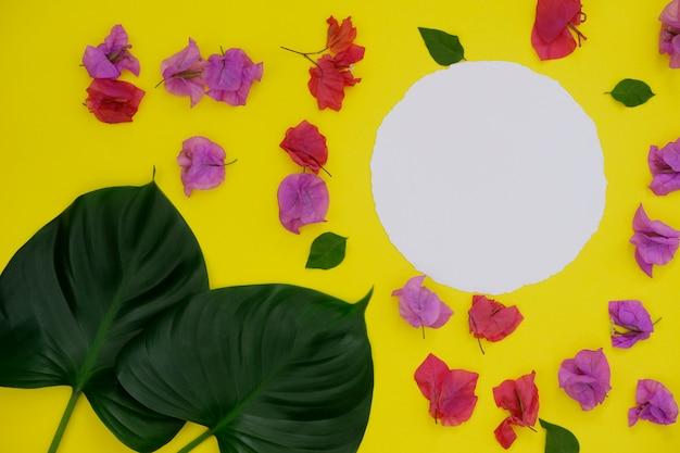 Maquette de papier blanc arrondi avec espace pour le texte ou l'image sur fond jaune et feuilles et fleurs tropicales.