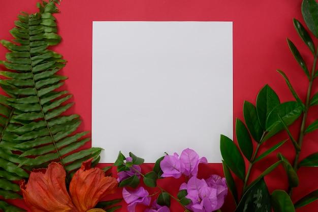Maquette de papier blanc avec un espace pour le texte ou l'image sur fond rouge et des feuilles et des fleurs tropicales