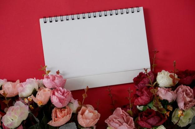 Maquette de papier blanc avec un espace pour le texte ou l'image sur fond rouge et fleur.