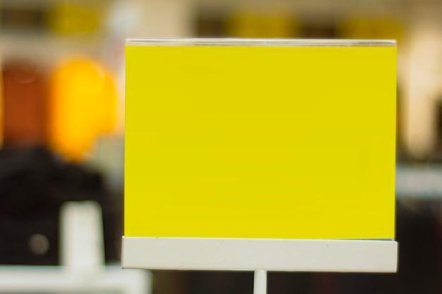 Maquette en papier jaune d'une enseigne de réduction sur le fond d'un magasin de vêtements.