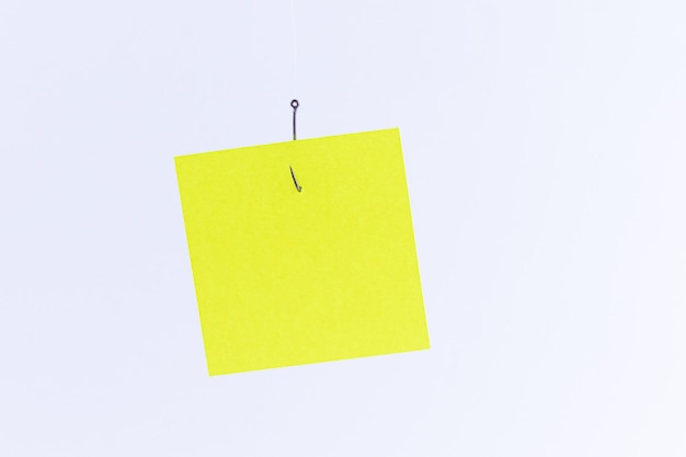 Maquette d'un papier mémo jaune vierge avec espace de copie accroché à un hameçon de pêche