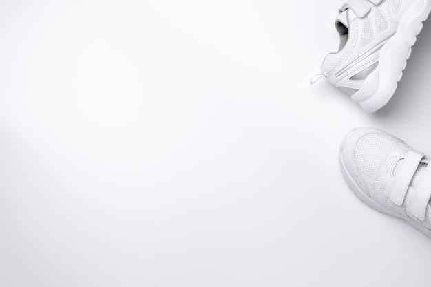 Maquette à plat pose deux baskets blanches sur le côté dans le coin avec espace de copie isolé sur un ba blanc ...
